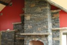 """Fireplace using our 6"""" snapped stone, with stone shelves and mantel and a carved Crowsfoot lintel"""