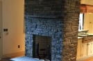 Fireplace with snapped facade, cleft hearth and satin planked flooring.